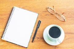 Vidrios, cuaderno, pluma negra, taza del café con leche en el fondo de madera de la tabla Fotografía de archivo libre de regalías