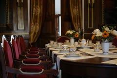 Vidrios de agua en la tabla elegante ajuste de la tabla en el castillo sillas del terciopelo y tazas de café Imágenes de archivo libres de regalías