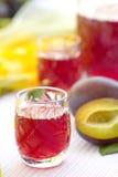 Vidrios de alcohol del ciruelo con los ciruelos Foto de archivo libre de regalías