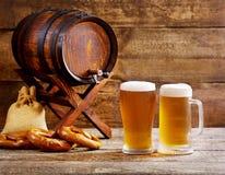 Vidrios de cerveza con el barril de madera Fotos de archivo libres de regalías