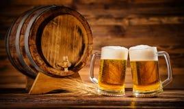 Vidrios de cerveza dorada con el barrilete de madera viejo Foto de archivo libre de regalías
