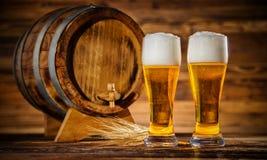 Vidrios de cerveza dorada con el barrilete de madera viejo Imagenes de archivo