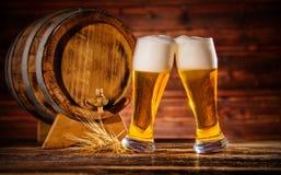 Vidrios de cerveza dorada con el barrilete de madera viejo Imagen de archivo libre de regalías