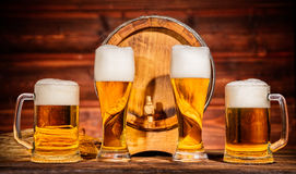 Vidrios de cerveza dorada con el barrilete de madera viejo Fotos de archivo libres de regalías