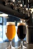 Vidrios de cerveza dorada y de oscuridad Imagen de archivo