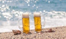 Vidrios de cerveza en la playa foto de archivo
