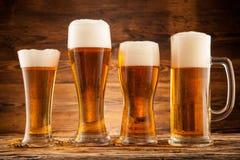 Vidrios de cerveza en tablones de madera Imagenes de archivo