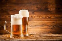Vidrios de cerveza en tablones de madera Foto de archivo