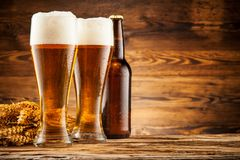 Vidrios de cerveza en tablones de madera Imagen de archivo libre de regalías