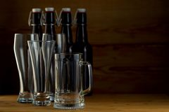 Vidrios de cerveza y botellas de cerveza en un fondo de madera Imagenes de archivo