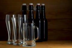 Vidrios de cerveza y botellas de cerveza en un fondo de madera Imagen de archivo
