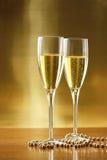 Vidrios de champán con el fondo del oro Imagenes de archivo