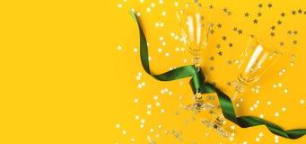 Vidrios de Champán con la cinta verde, confeti de oro en la forma de las estrellas en la opinión superior puesta plano amarillo d imagen de archivo