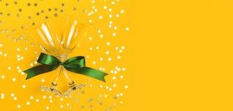 Vidrios de Champán con la cinta verde, confeti de oro en la forma de las estrellas en la opinión superior puesta plano amarillo d fotografía de archivo
