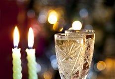 Vidrios de champán con la vela en bokeh Foto de archivo libre de regalías