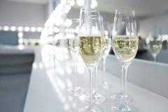 Vidrios de Champán en el fondo blanco en luces brillantes Fotografía de archivo libre de regalías