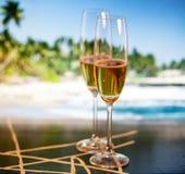 Vidrios de Champán en la playa tropical - Año Nuevo exótico Fotos de archivo libres de regalías