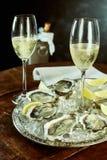 Vidrios de champán y de ostras en la tabla Imágenes de archivo libres de regalías