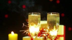 Vidrios de chisporrotear el champán en un fondo de fuegos artificiales de las luces de Bengala almacen de metraje de vídeo