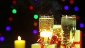 Vidrios de chisporrotear el champán en un fondo de fuegos artificiales de las luces de Bengala metrajes
