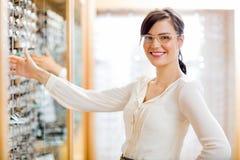 Vidrios de compra del cliente femenino en el óptico Store fotografía de archivo libre de regalías