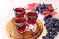 Vidrios de jugo de uva con hielo y uvas negras Imagenes de archivo