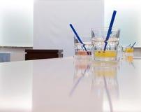 Vidrios de jugo en la sala de conferencias fotos de archivo