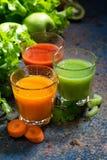 Vidrios de jugo de las verduras frescas de zanahorias, de los tomates y de la hierba Imágenes de archivo libres de regalías