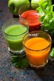 Vidrios de jugo de las verduras frescas de zanahorias, de los tomates y de la hierba Imagen de archivo