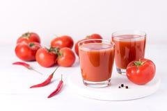 Vidrios de jugo de tomate sabroso con los tomates crudos en la bebida de madera blanca del Detox de la dieta sana del fondo Fotos de archivo libres de regalías