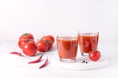 Vidrios de jugo de tomate sabroso con los tomates crudos en la bebida de madera blanca del Detox de la dieta sana del fondo Fotografía de archivo