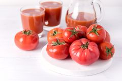 Vidrios de jugo de tomate sabroso con los tomates crudos en la bebida de madera blanca del Detox de la dieta sana del fondo Imagenes de archivo