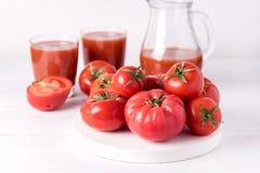Vidrios de jugo de tomate sabroso con los tomates crudos en la bebida de madera blanca del Detox de la dieta sana del fondo Imagen de archivo
