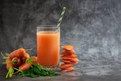 Vidrios de jugo de zanahoria con las verduras en la tabla gris Vista lateral imagen de archivo libre de regalías