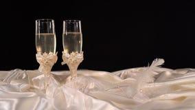 Vidrios de la boda con el champange chispeante en una tabla