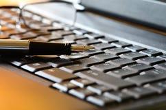 Vidrios de la pluma y de lectura en un ordenador portátil Foto de archivo libre de regalías