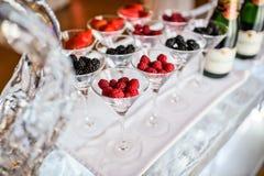 Vidrios de las frambuesas, fresas, zarzamoras en la barra del hielo Cena de gala en el restaurante foto de archivo