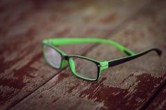 Vidrios de las lentes en el dackground de madera del escritorio Imagen de archivo