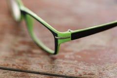 Vidrios de las lentes en el dackground de madera del escritorio Foto de archivo libre de regalías