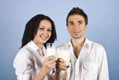 Vidrios de leche felices de la explotación agrícola de los pares de la juventud Foto de archivo