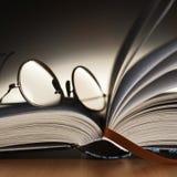 Vidrios de lectura en el libro imágenes de archivo libres de regalías