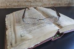 Vidrios de lectura en la biblia muy vieja Fotos de archivo