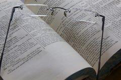 Vidrios de lectura en un libro abierto Fotos de archivo libres de regalías