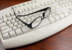 Vidrios de lectura en un teclado blanco Imagen de archivo libre de regalías