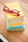Vidrios de lectura rojos en la pila de libros Fotografía de archivo libre de regalías