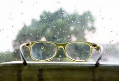 Vidrios de lectura verdes sobre la ventana lluviosa Fotos de archivo libres de regalías