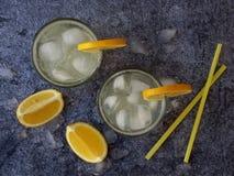 Vidrios de limonada hecha en casa fría con las rebanadas del limón, los cubos de hielo y la paja en fondo oscuro Copie el espacio Imagen de archivo