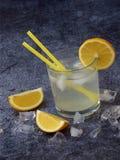 Vidrios de limonada hecha en casa fría con las rebanadas del limón, los cubos de hielo y la paja en fondo oscuro Copie el espacio Imágenes de archivo libres de regalías