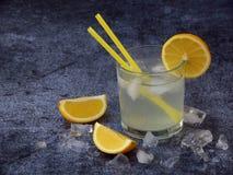 Vidrios de limonada hecha en casa fría con las rebanadas del limón, los cubos de hielo y la paja en fondo oscuro Copie el espacio Imagenes de archivo