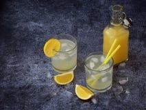 Vidrios de limonada hecha en casa fría con las rebanadas del limón, los cubos de hielo y la paja en fondo oscuro Copie el espacio Fotografía de archivo libre de regalías